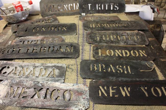 Maschere di metallo con i nomi dei principali porti di destinazione delle noci moscate di Gouyave